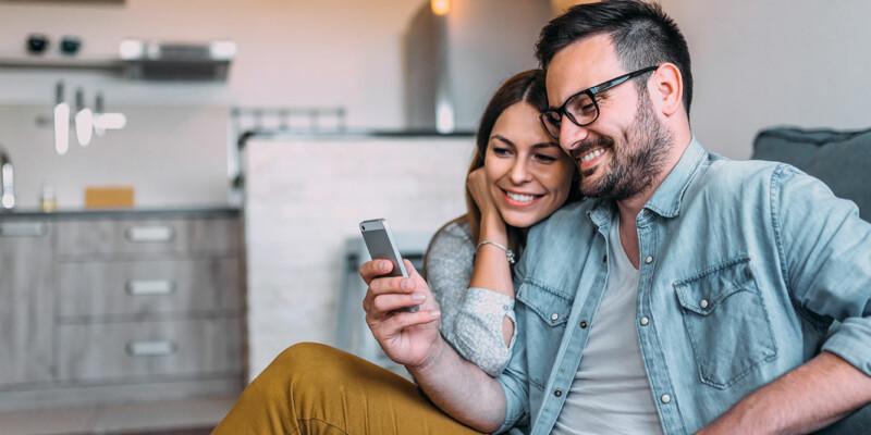 Junges Paar sitzt am Sofa und schaut aufs Smartphone